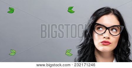 Green Leaves With Young Businesswoman In A Thoughtful Face