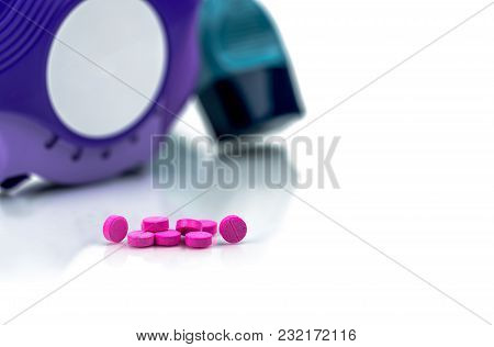 Pile Of Round Pink Small Tablets Pills On Blurred Background Of Asthma Inhaler An Accuhaler. Broncho