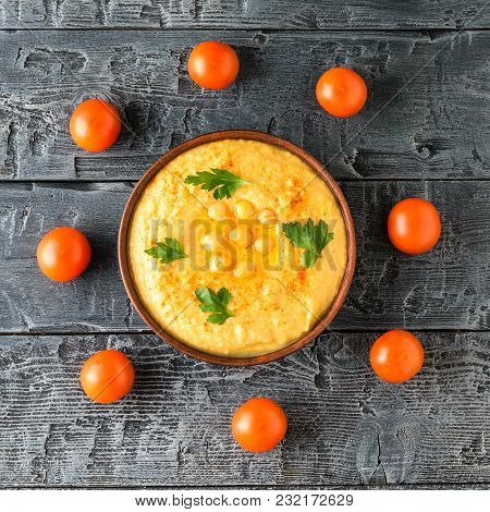 Bowl With Fresh Hummus And Eight Cherry Tomatoes On A Wooden Table. Vegetarian Middle Eastern Dish A