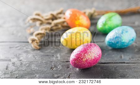 Five Colorful Eggs And A Branch Of Willow On A Dark Wooden Table. The Decoration Of The Easter Table