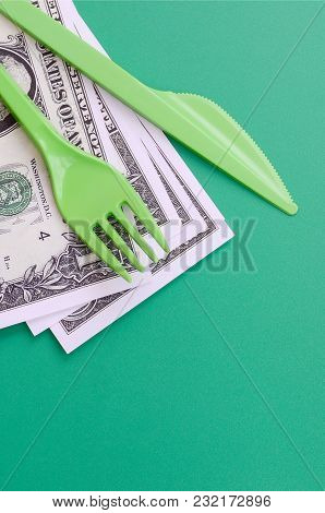 Disposable Plastic Cutlery Green. Plastic Fork And Knife Lie On A Small Amount Of Us Dollars