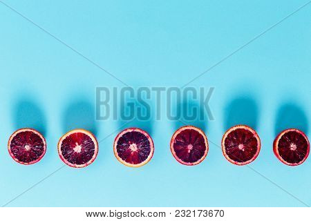 Red Oranges On The Bold Blue Background. Creative Minimalism And Modern Food Pattern Concept