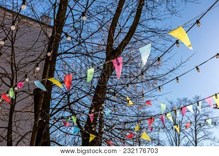 Colorful Triangular Flags Fluttering On Tree Branches Against Clear Blue Spring Sky. Decoration For