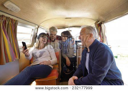 Group of senior friends in camper van using smartphone