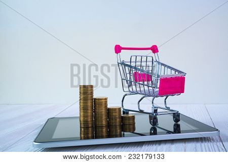 Step Of Coin Stack And Shopping Cart Or Supermarket Trolley On Tablet Computer Screen On White Worki