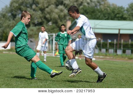 KAPOSVAR, HUNGARY - SEPTEMBER 5: Janos Balogh (white 10) in action at the Hungarian National Championship under 17 game Kaposvar (white) vs. Nagyatad (green) September 5, 2011 in Kaposvar, Hungary.