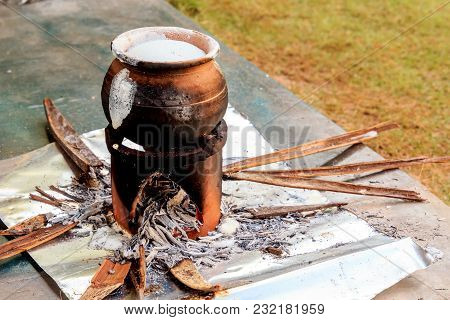 Traditional Indian And Lankan Clay Pot For Cooking Coconut Milk On An Open Fire. Palm Leaves, Nutshe