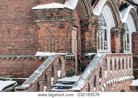 The Facade Of An Old Vintage Brick Building With A Staircase. Railings And Windows In The Snow.
