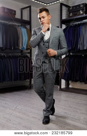 Sale, Shopping, Fashion, Style And People Concept - Elegant Young Man Choosing And Trying Jacket On
