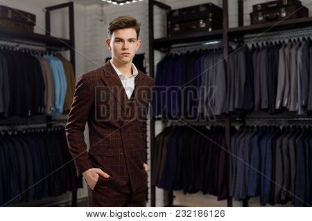Businessman In Classic Vest Against Row Of Suits In Shop. A Young Stylish Man In A Jacket. It Is In