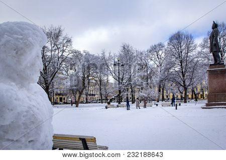 Monument to poet Alexander Pushkin (sculptor Anikushin) on Square of Arts in St. Petersburg in winter and Pushkin's sculpture made of snow (snowman), Russia