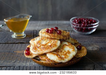 Russian-style Fritters With Honey And Cowberries On Dark Wooden Background