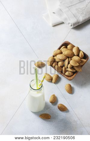 Homemade Almond Milk And Raw Almond In The Sinks In A Wooden Bowl On A White Background, Selective F