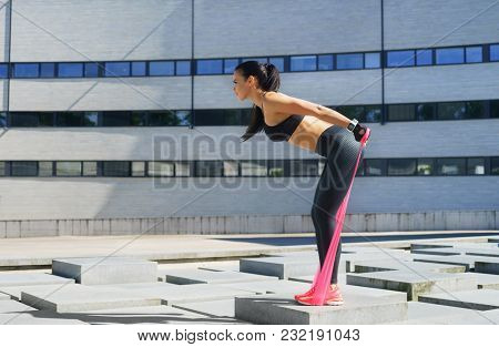 Young and sporty girl training with elastic band outdoor.