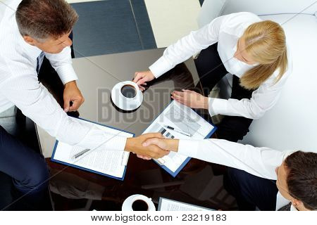Image of successful partners handshaking after negotiations