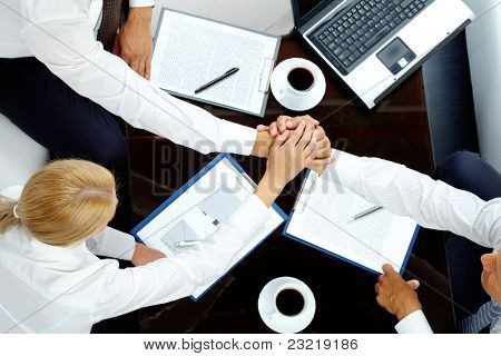 Image of successful partners making pile of hands over workplace