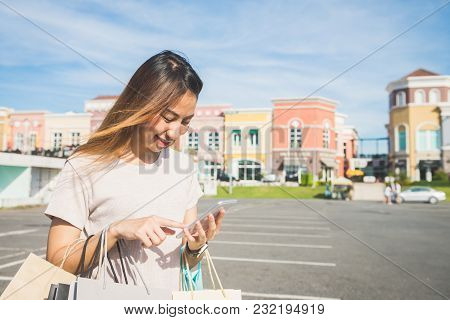 Close Up Of A Young Woman Hold A Shopping Bags In Her Hand And Chatting On Her Phone After Shopping.