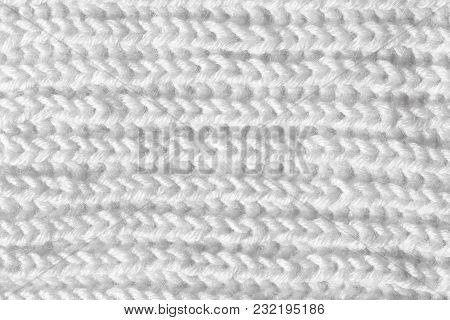 The Sample Of A Knitted Cloth Of White Color. Texture Of Woolen Threads, The Product Is Made By Hand