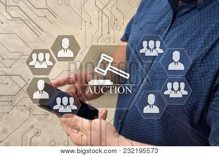 Online Auctions  On The Touch Screen With A Blur Background Of The Businessman With The Phone.the Co