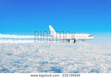 Passenger Plane Flying At Flight Level With The Contrails Of The Engines Above The Clouds Blue Sky