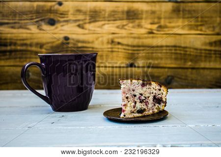 A Cup Of Tea And Piece Of Pie On Wooden Background
