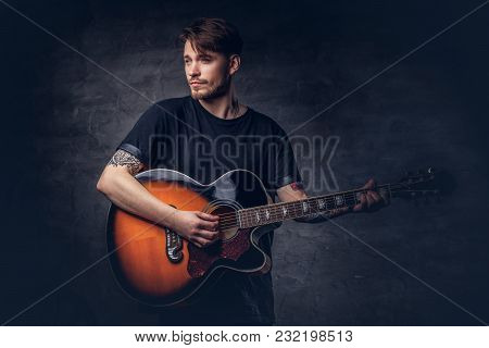 An Attractive Tattooed Guitarist In Black T-shirt Playing On Acoustic Guitar, Isolated On A Dark Bac