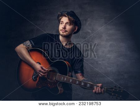 An Attractive Tattooed Guitarist In Hat Playing On Acoustic Guitar, Isolated On A Dark Background.