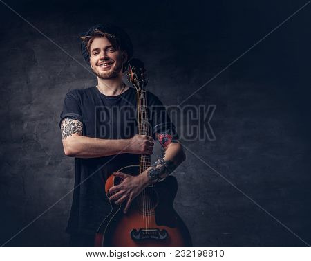 A Handsome Tattooed Guitarist In Black T-shirt Holds An Acoustic Guitar, Isolated On A Dark Backgrou