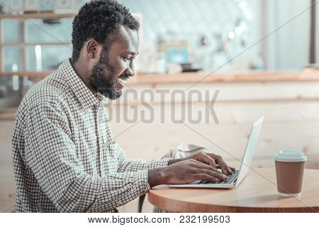 Interesting Job. Happy Positive Nice Freelancer Looking At The Netbook Screen And Typing While Enjoy