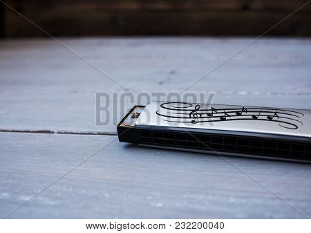 A Silver Harmonica On A Wooden Background