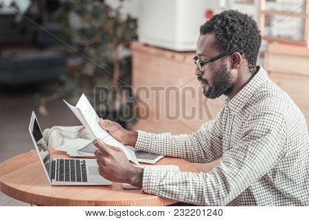 University Studies. Serious Intelligent Nice Man Sitting At The Table And Reading Lecture Notes Whil