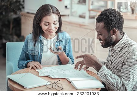 University Preparation. Pleasant Smart Young Woman Sitting At The Table And Looking At Her Notes Whi