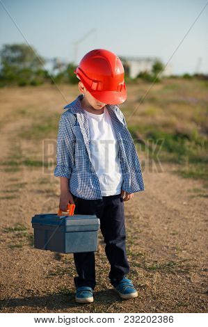 Sad Little Working Kid In Orange Helmet Hung His Head With Tool Case In One Hand