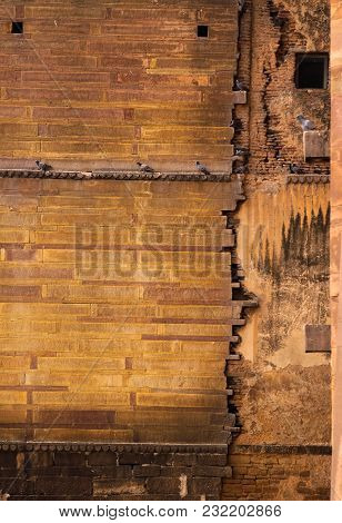 Colorful Vintage Bricks On The Side Of A Bright Old Yellow Wall With A Perched Flock Of Pigeons On I