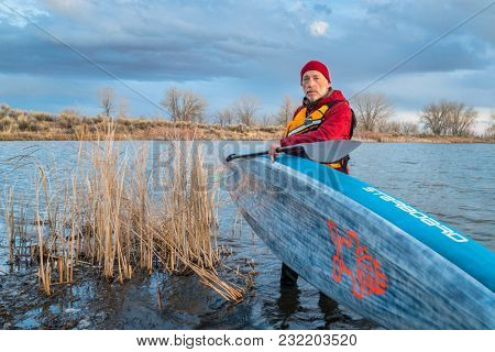 Fort Collins, CO, USA - March 19, 2018:  A senior male paddler launching his racing All Star stand up paddleboard (2018 model by Starboard) on a lake shore in early spring scenery.