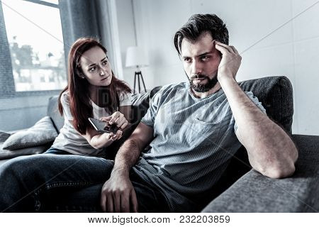 What Is This. Interested Worried Redhead Woman Sitting On The Sofa Near Her Husband Holding Cellphon