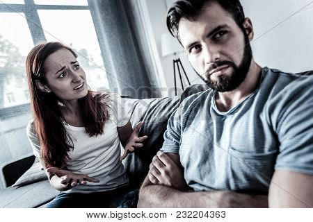 Big Problems. Anxious Worried Redhead Woman Sitting At Home On The Sofa Gesticulating And Asking Her