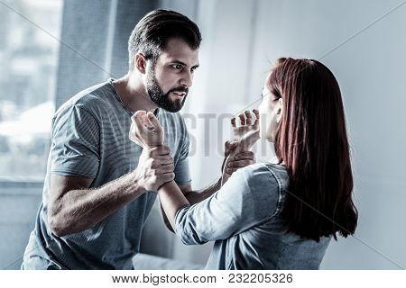 Brute Force. Angry Evil Unshaken Man Standing In The Bright Room Feeling Bed Himself And Holding Wom