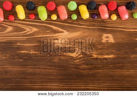 Color Fruit Candy On Dark Wooden Background With Copespace