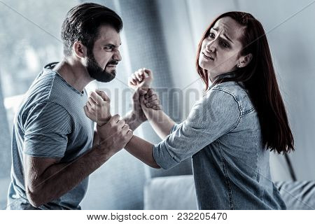 Feeling Pain. Worried Redhead Exhausted Woman Standing Opposite Man Who Holding Her Hands Looking As
