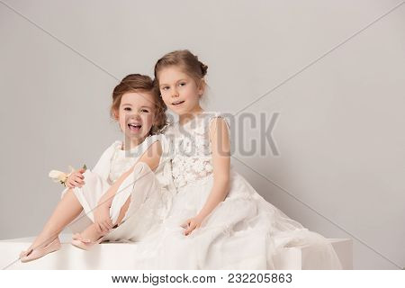Little Pretty Girls With Flowers Dressed In Wedding Dresses. Lovely Little Girlfriends. Girls Dreami