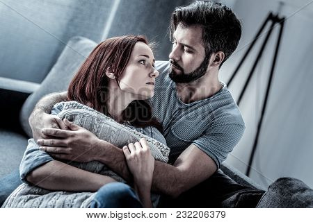 Do You Love Me. Cute Calm Young Woman Sitting On The Sofa Hugging Pillows And Looking At Her Husband