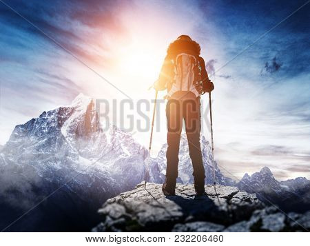 Backpacker or hiker in the Alps in winter standing on a mountain summit facing a bright sun flare in a blue sky over high snow-capped peaks in a dramatic conceptual image