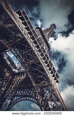 Low-angle view of Eiffel Tower against dramatic cloudy sky, landmark and French tourist attraction in Paris, France