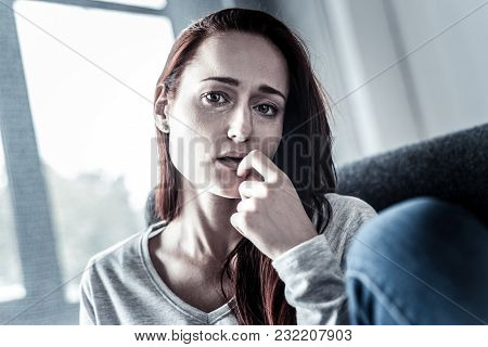 Im In Trouble. Depressed Upset Redhead Woman Feeling Bed Herself Holding Hand Near Mouth And Looking