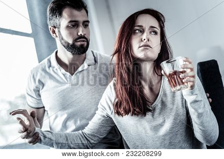 Want To Be Alone. Stressful Frustrated Serious Woman Sitting On The Sofa Drinking Alcohol And Turnin