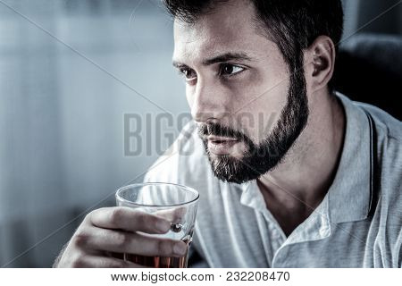 One More Glass. Thoughtful Concentrated Beardful Man Sitting In The Empty Room Looking Aside And Dri