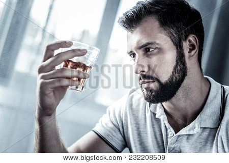 Im Alone. Sad Upset Beardful Man Spending Time Alone In The Bright Room Holding And Looking At The G