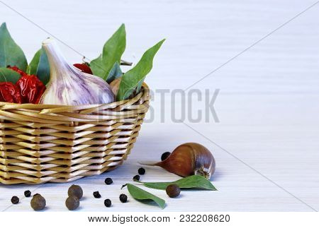 Background And Spices. The Bay Leaf In A Wicker Basket, Garlic And Hot Chilli Pepper.