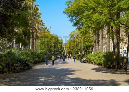 BARCELONA, SPAIN - FEBRUARY 23, 2018: People walking by the Rambla del Raval, a pedestrian street named after the popular district of El Raval, close to the La Rambla